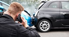 Young Male Motorist Involved In Car Accident Calling Insurance Company Or Recovery Service