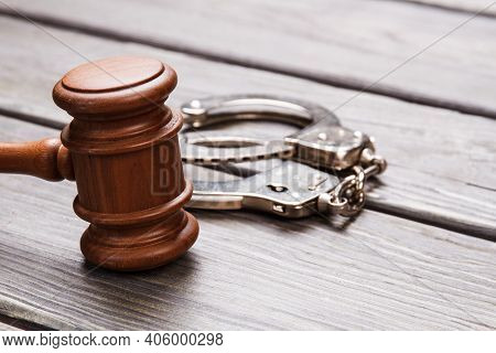 Close-up Gavel And Handcuffs. Wooden Hammer And Metal Handcuffs On The Desk.