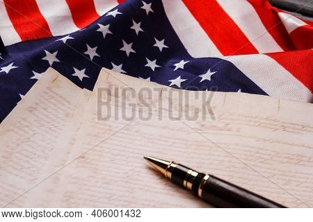 Concept Of The United States Declaration Of Independence. Pen With Old Pages And Flag Of The Usa.