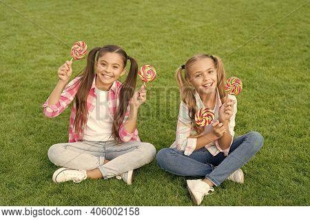 Candy Girls. Happy Children Hold Candy Green Grass. Candy Shop. Lollipop Or Sucker On Sticks. Sugary