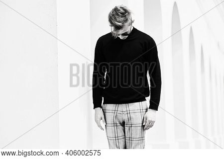 Art fashion portrait. Handsome blond man model in black pullover and black sunglasses stands next to white columns in the old town and looks down. Black-and-white portrait.