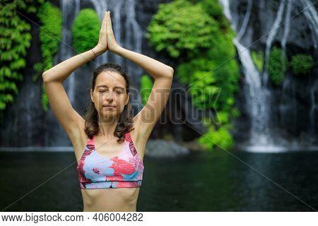 Hands Raising Up In Namaste Mudra. Yoga Near Waterfall. Young Woman Meditating, Practicing Yoga And