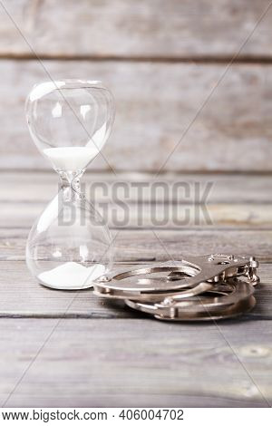Serve Sentence Concept. Hourglass And Handcuffs On Wooden Background.