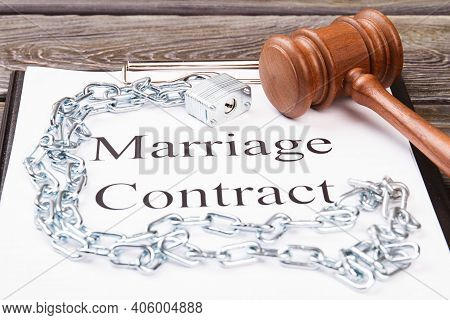 Concept Of Marriage As A Prison. Marriage Contract With Metal Chains And Wooden Gavel.