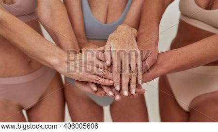 Unity Of Women. Close Up Of Mature Women In Underwear Putting Their Hands On Each Other As Sign Of U