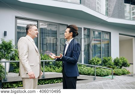 Serious Businessmen Standing Outside The Office Building And Discussing News And Ideas