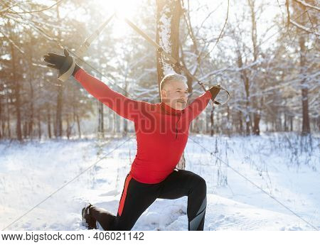Trx Suspension Training Concept. Athletic Senior Man Working Out With Sports Equipment On Snowy Wint