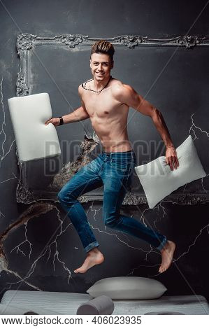 Smiling Man With Two White Pillows In Hands Jumping On A Mattress On A Gray Background. Concept Of C