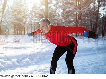 Outdoor Winter Strength Training Concept. Positive Senior Sportsman With Dumbbells Doing Powerliftin