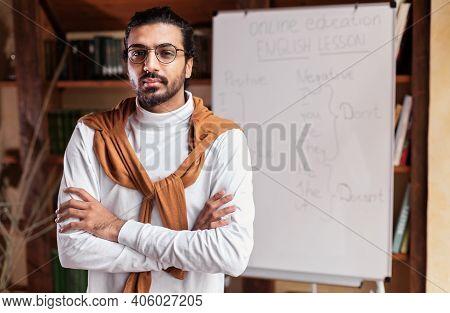 Portrait Of Serious Indian Teacher Man Posing Standing Near Blackboard Teaching English Online Indoo
