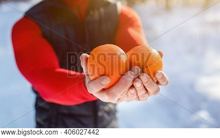 Closeup Of Fit Mature Man Holding Oranges As Healthy Snack After Morning Workout At Snowy Winter For