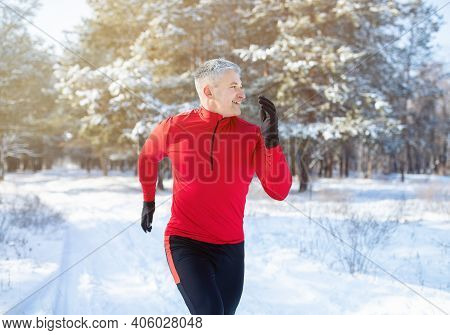 Mature Trail Runner Training For Marathon In Beautiful Snowy Forest. Senior Male Athlete Jogging And