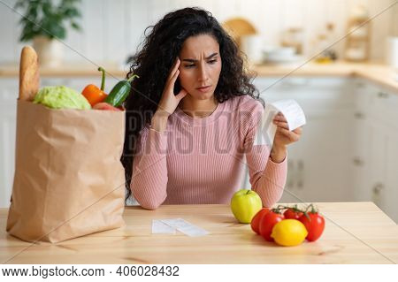 Grocery Expenses. Concerned Brunette Woman Sitting At Table In Kitchen, Looking At Bill After Food S