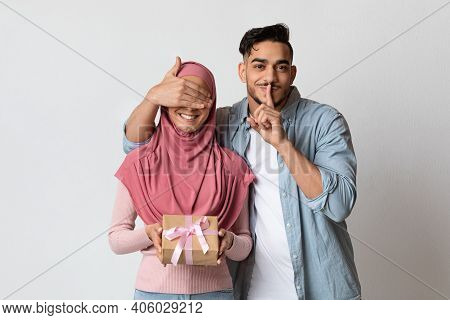 Surprise Present. Loving Arab Man Covering His Muslim Girlfriends Eyes, And Showing Shh Silence Sign