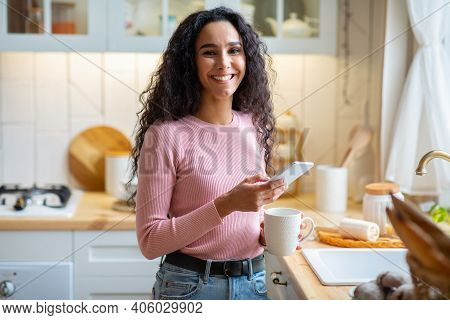 Portrait Of Cheerful Young Woman Drinking Morning Coffee And Using Smartphone In Kitchen. Happy Brun