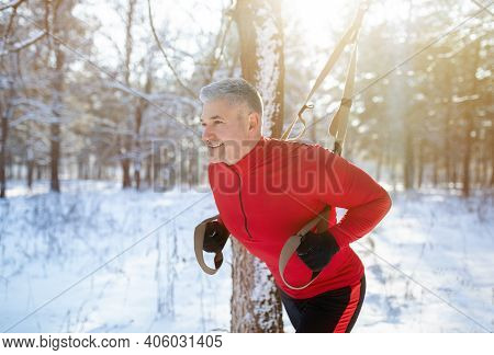 Strong Mature Man Doing Trx Fitness Workout At Snowy Winter Park. Senior Man Engaged In Suspension W
