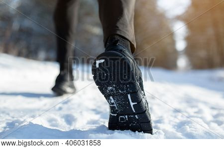 Cropped View Of Sportsman Jogging On Snowy Road In Winter, Closeup Of Feet In Sneakers, Copy Space.