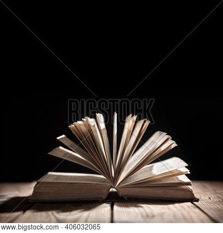 Old book or open Holy Bible on a table with spot light concept for reading, storytelling and education or bible and religion, black backround space above for text message or copy