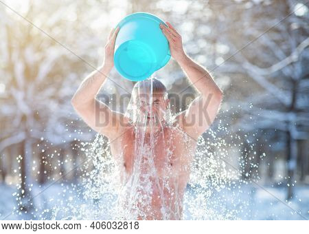 Senior Man Pouring Water From Bucket Onto His Head, Tempering His Body At Snowy Winter Park. Healthy