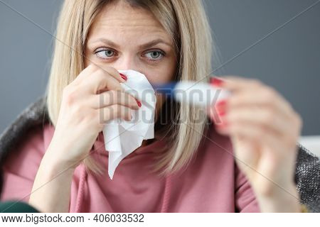 Sick Woman Holding Infrared Thermometer And Paper Napkin. Ambulatory Treatment Concept