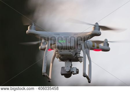 Great Malvern, United Kingdom, 27th December, 2020: Drone Quadcopter Hovering In Front Of Trees And