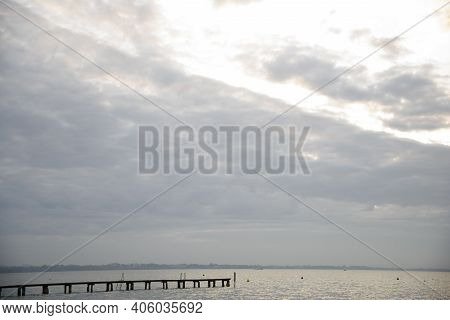 Lake At Sunset With Clouds And Wooden Jetty. Sailboats In The Waves.