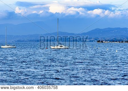 Lake At Sunset With Clouds And Mountain Profiles With Sailboats.