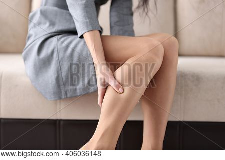 Woman Siting On Couch And Holding Shin With Her Hand Closeup. Prevention Of Varicose Veins Concept