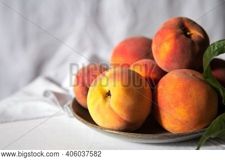 Peaches With Leaves Still Life On Color Green Plate On Table With White Tablecloth. Ripe Juicy Peach