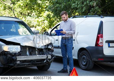 Man Insurance Agent With Auto Insurance Blank Against Destroyed Car In Car Crash Traffic Accident On