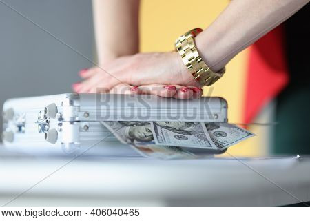 Female Hands Closing Metal Suitcase With Dollar Bills Closeup. Illegal Enrichment Concept