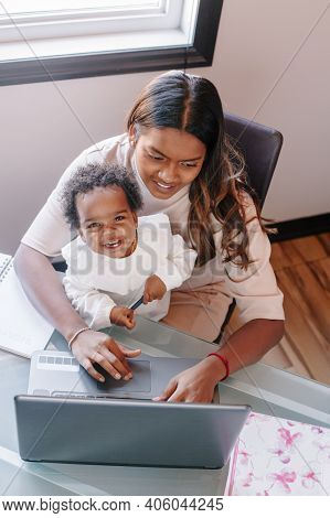 Mixed Race Indian Mother With African Black Baby Working Online From Home On Internet. Workplace Of