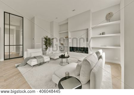 A Cozy Living Room In White With Sofa And Shelves On The Wall. Luxury Interior Design Of Modern Hous