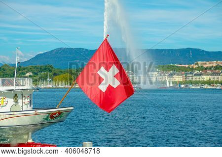 Swiss Flag In Foreground And Jet Deau Fountain In Geneva Lake On Background, The Most Famous Attract