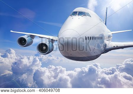 Modern Plane In The Clouds Against Blue