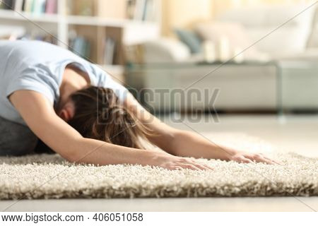 Close Up Of Female Doing Yoga Child Pose On A Carpet In The Living Room At Home