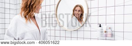 Cheerful Woman In Bathrobe Smiling While Looking At Mirror In Bathroom, Banner