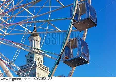 A Beautiful And Scenic View Of The Empty Cabins Of The Ferris Wheel Against The Blue Sky And The Spi