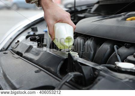 Man Filling Car Radiator With Antifreeze Outdoors, Closeup