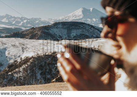 A Woman In Winter Clothes Drinks Hot Tea In The Mountains. Tourist In Nature. Mulled Wine With Mount