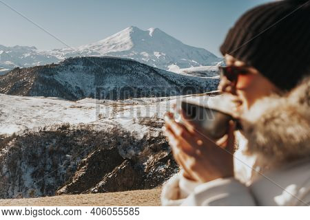 Beautiful Woman In A Winter Jacket Against The Backdrop Of Snow-white Mountains.