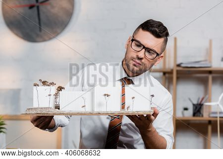 Serious Architect Holding Houses Models In Architectural Bureau