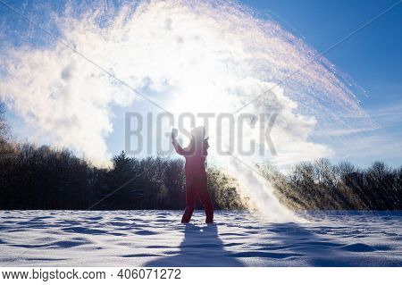 Unrecognisable Person Pouring Hot Water Up In The Sky, Sunny Winter Day. Boiling Water Challenge, Wh