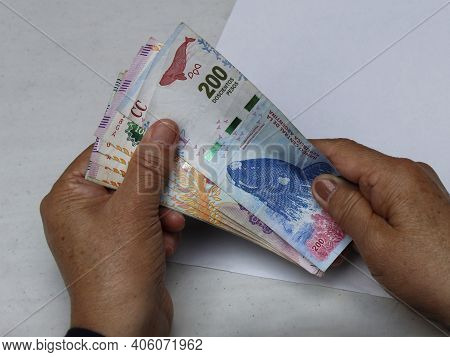 Hands Of A Senior Woman Holding Argentine Banknotes