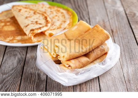 Frozen Pancakes In A Plastic Bag On A Wooden Background. Semi-finished Pancakes With Filling