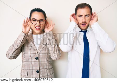 Beautiful couple wearing business clothes trying to hear both hands on ear gesture, curious for gossip. hearing problem, deaf