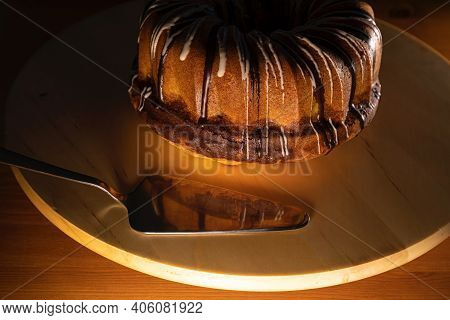 brown sugar coated bundt cake on a white turntable with silver cake shovel, image is focused on the front of the cake and the shovel, warm low light atmosphere