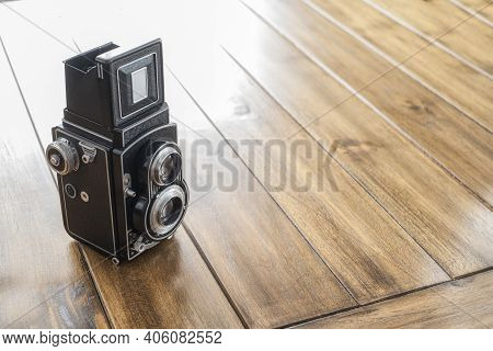 Close-up Of An Old Twin Lens Reflex Camera, On A Wooden Table, With Copy Space, Vintage And Antique