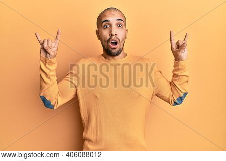 Hispanic adult man doing rock gesture over yellow background afraid and shocked with surprise and amazed expression, fear and excited face.