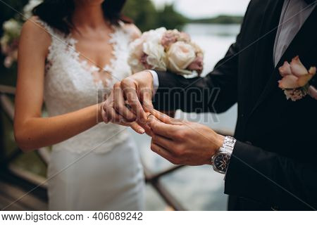 Wedding Engagement Rings. Married Couple Exchange Wedding Rings At A Wedding Ceremony. Groom Put A R